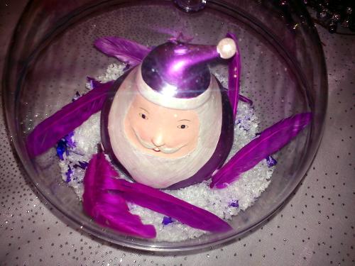 Centre de table réalisé à partir d'une boule en plastique transparente, de neige, de graviers, de plumes et d'une boule de Noël géante